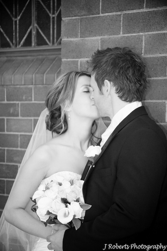 Bride and groom kissing - wedding photography