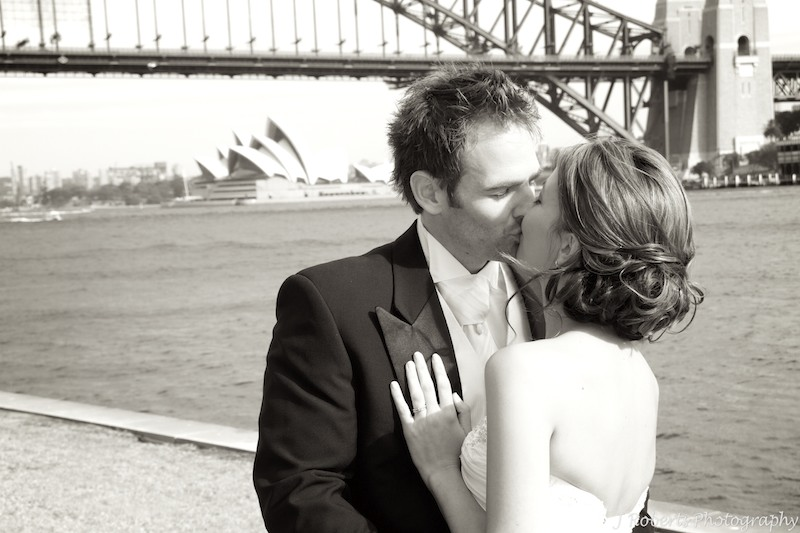 Bride and groom kissing with Sydney Harbour Bridge - wedding photography