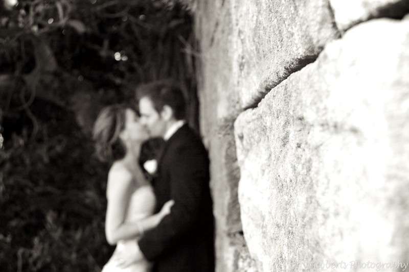 B&W bride and groom at sandstone wall - wedding photography