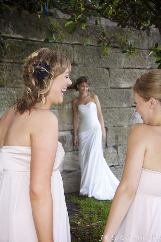 Bridesmaids laughing with bride in background - wedding photography