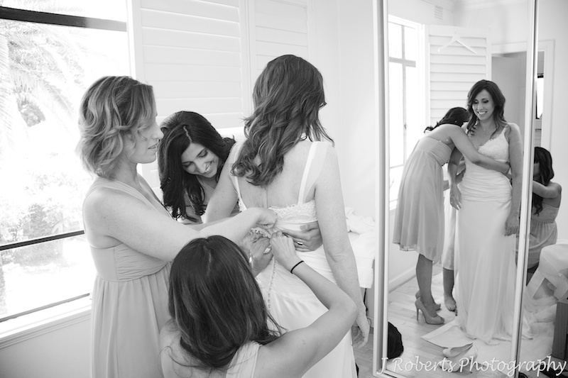 Bridesmaids helping the bride into her dress - wedding photography sydney