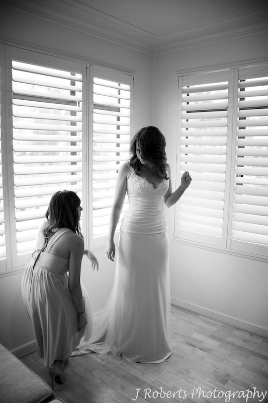 Bride having her dress laid out by bridesmaid - wedding photography sydney
