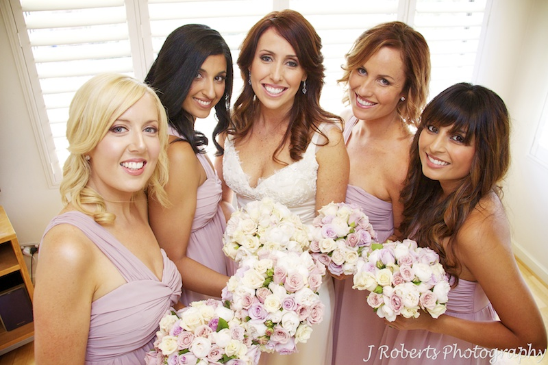 Bride and bridesmaids looking stunning smiling up at camera - wedding photography sydney