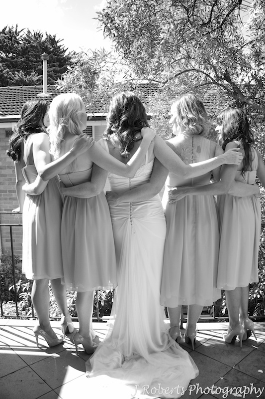 Bride and bridesmaids with their arms around each other - wedding photography sydney