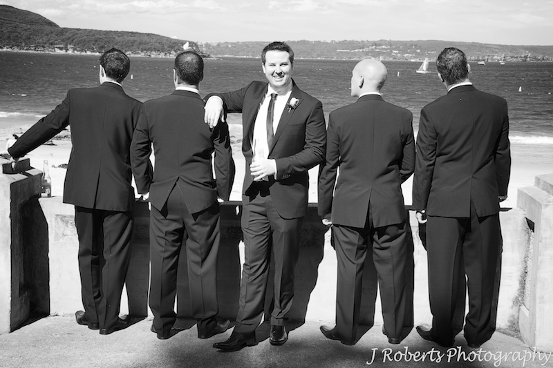 B&W of groom facing camera with groomsmen looking out to sea - wedding photography sydney