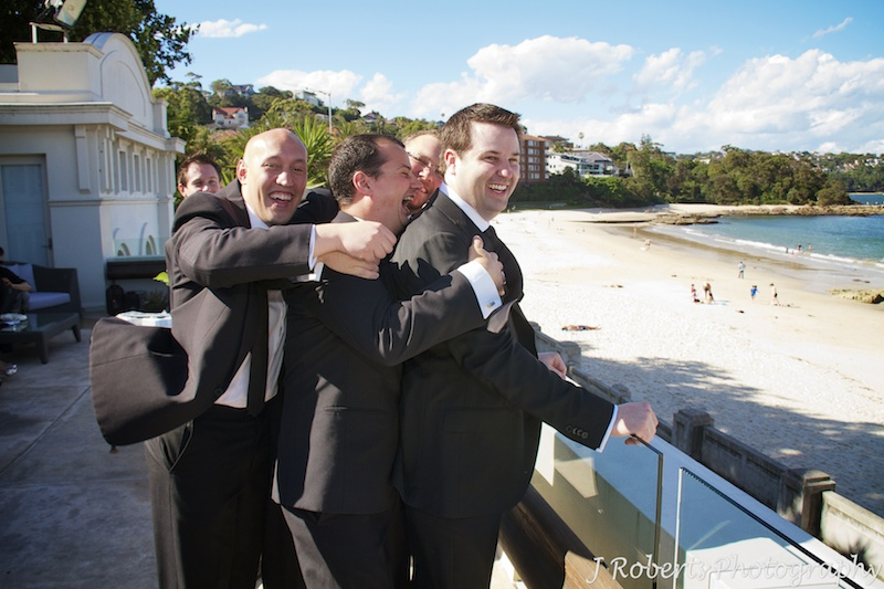 Groomsmen holding groom back from leap before wedding - wedding photography sydney