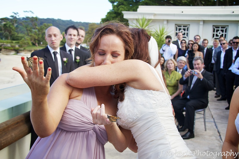 Bride and her sister hugging during ceremony in memory of their Mum - wedding photography sydney