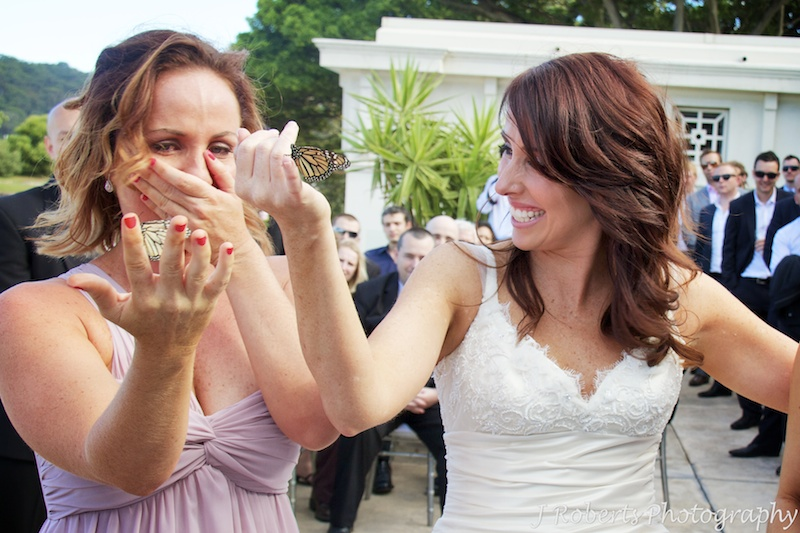 Bride and her sister crying during buffer fly release ceremony - wedding photography sydney