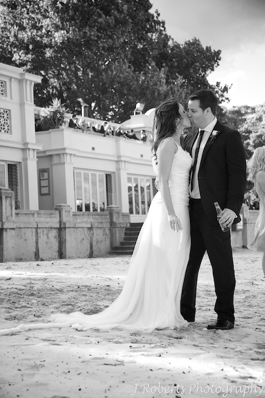 Bride and groom kissing on Balmoral Beach with guests on Bather's Pavilion behind them - wedding photography sydney
