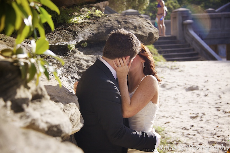 Bride and groom kissing agains rock wall - wedding photography sydney
