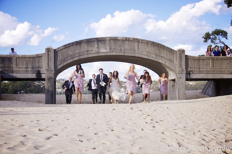 Bridal party running under the bridge at Balmoral Beach - wedding photography sydney
