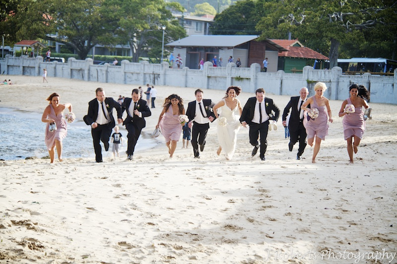 Bridal party start running race on beach - wedding photography sydney