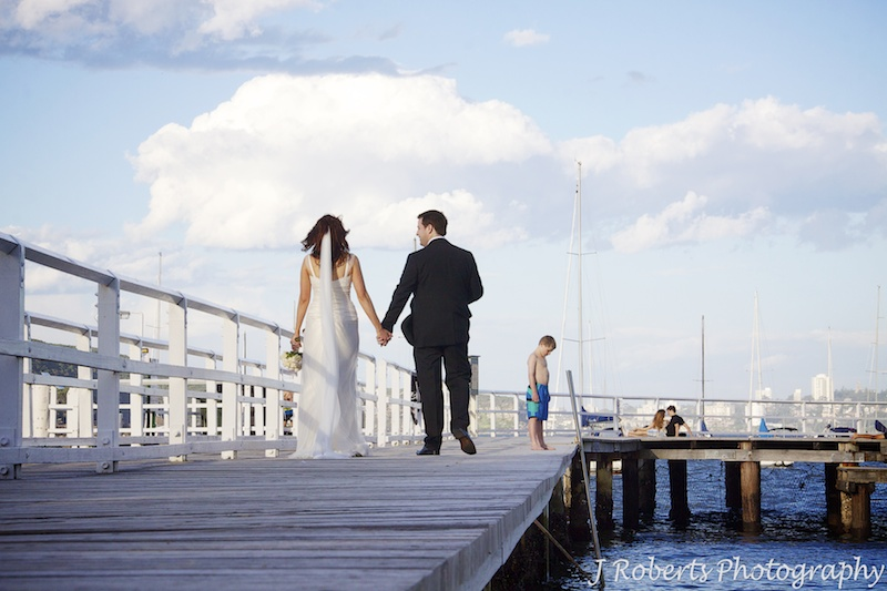 Bride and groom walking along the boardwalk at Balmoral Baths - wedding photography sydney