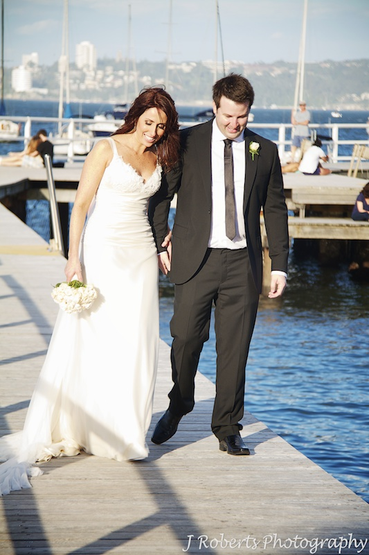 Bride and groom walking hand in hand in afternoon sunlight - wedding photography sydney