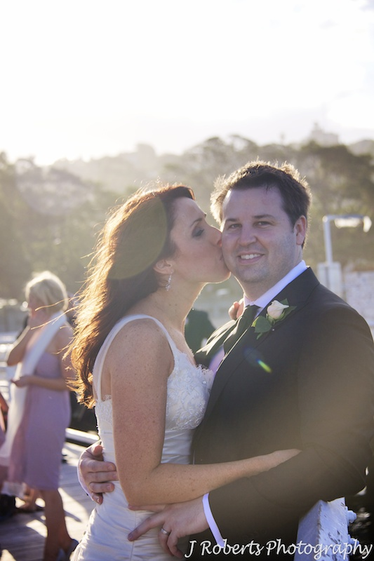 Bride kissing groom with setting sun behind - wedding photography sydney