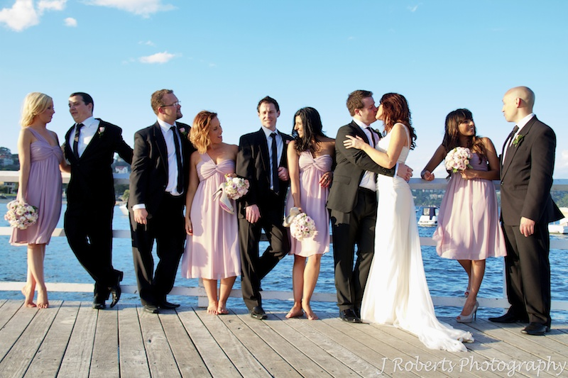 Bridal party chatting in a line with the couple kissing in the middle - wedding photography sydney