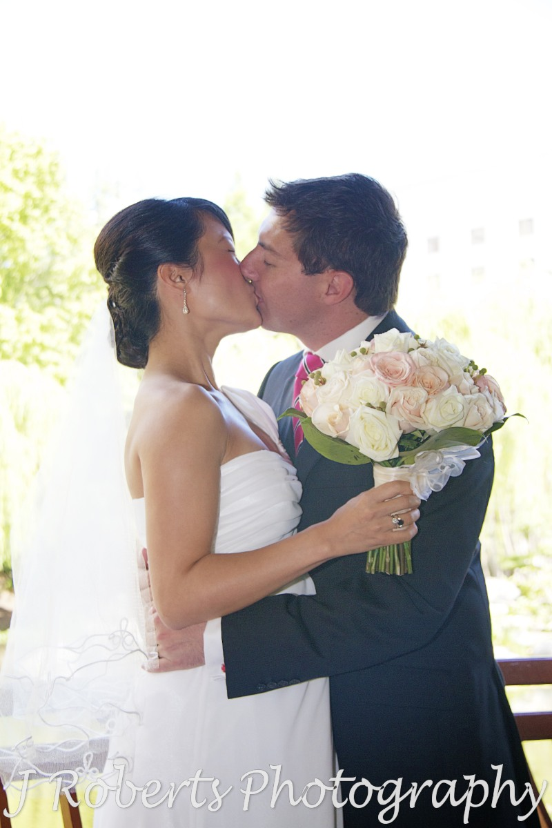 Bride and grooms first kiss as married couple - wedding photography sydney