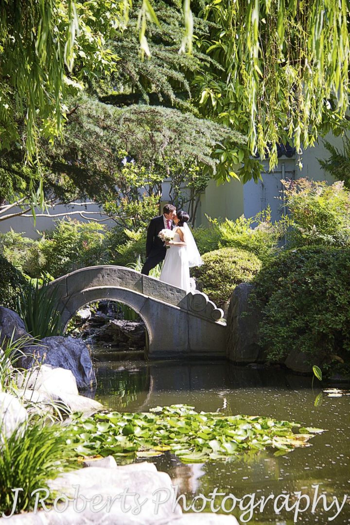 Bride and groom kissing on a bridge in the chinese gardens sydney - wedding photography sydney