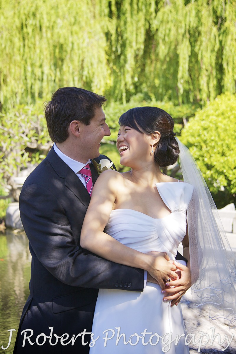 Bride and groom laughing at each other - chinese gardens sydney - wedding photography sydney