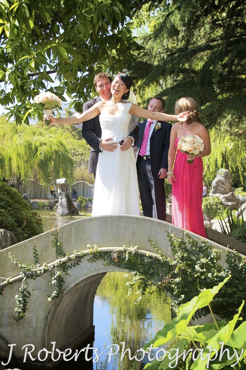 Groom holding bride on bridge at chinese gardens sydney - wedding photography sydney