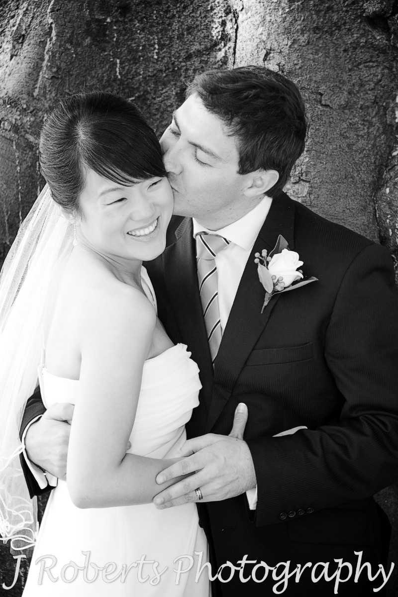 Groom kissing smiling bride - wedding photography sydney