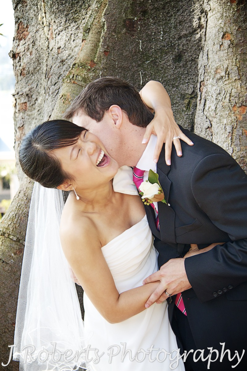 Bride laughing as groom kisses her neck - wedding photography sydney