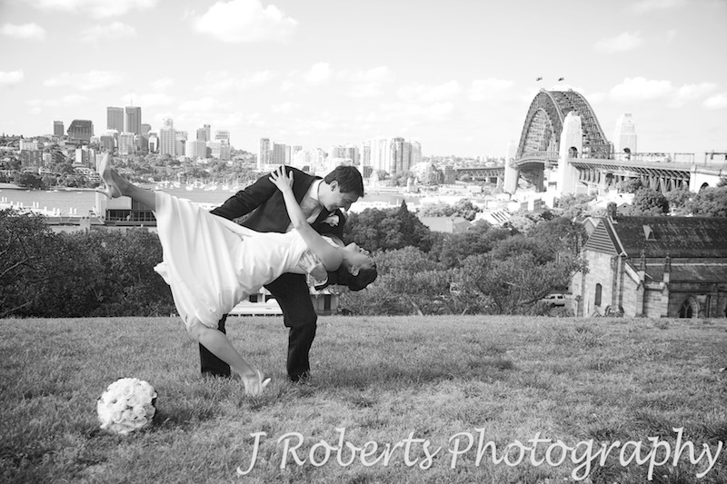 Groom dipping bride with Sydney Harbour and bridge in the background on Observatory Hill - wedding photography sydney