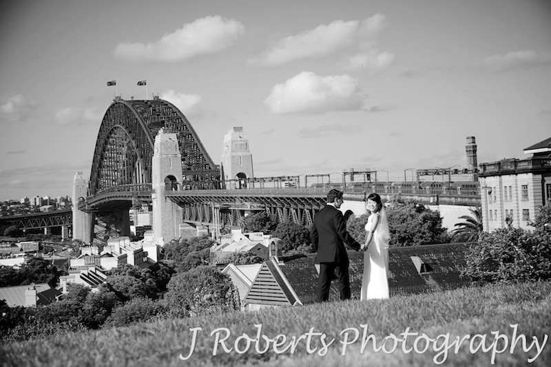 Bride and groom looking back over shoulder while walking down observatory sydney - wedding photography sydney