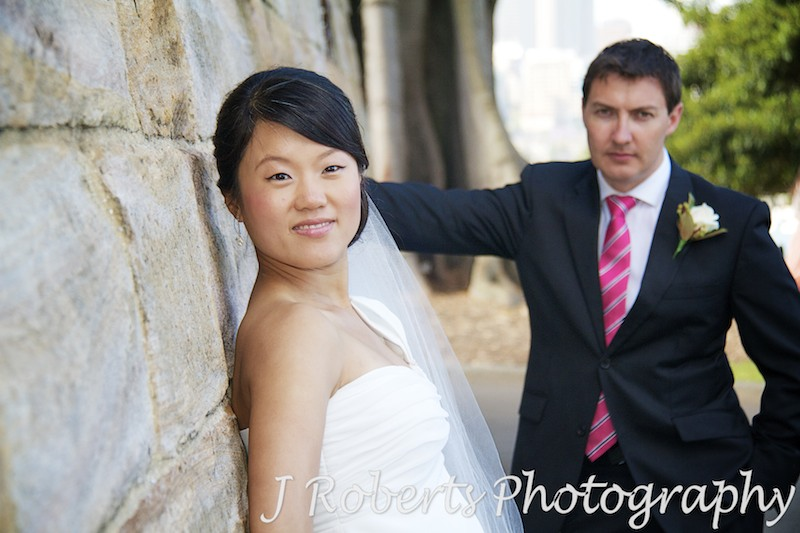 Bride looking along a wall at the camera with groom behind - wedding photography sydney