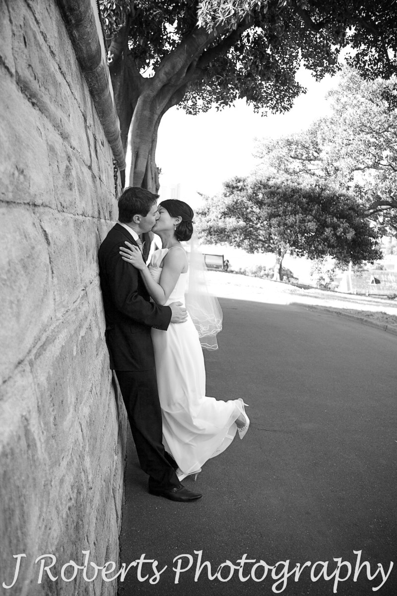 Bride and groom kissing up again the wall of the Observatory Sydney - wedding photography sydney