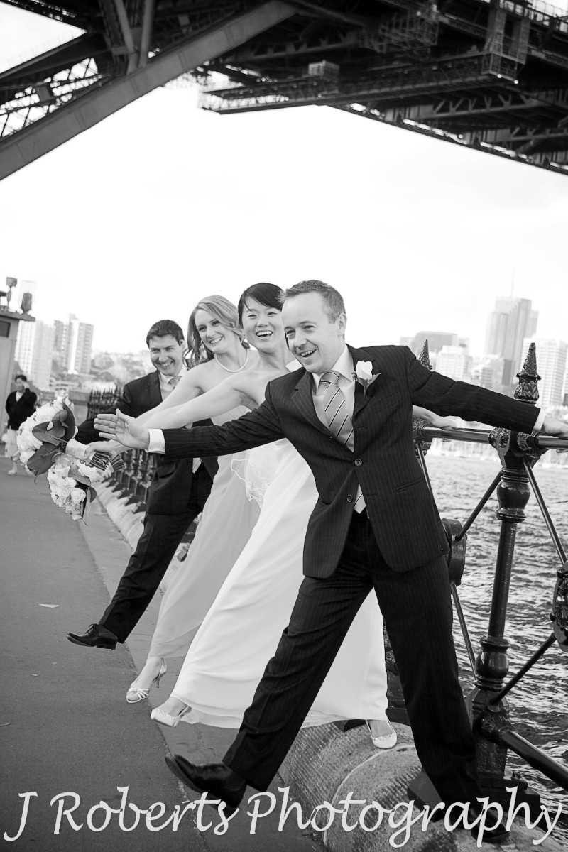 Bridal party swinging off the fence at Dawes Point - wedding photography sydney