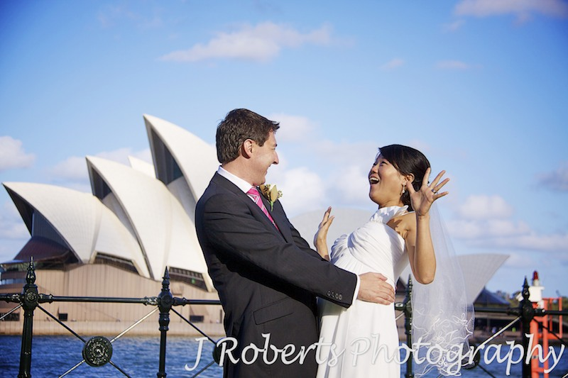 Bride looking shocked at groom Dawes Point in front of opera house - wedding photography sydney