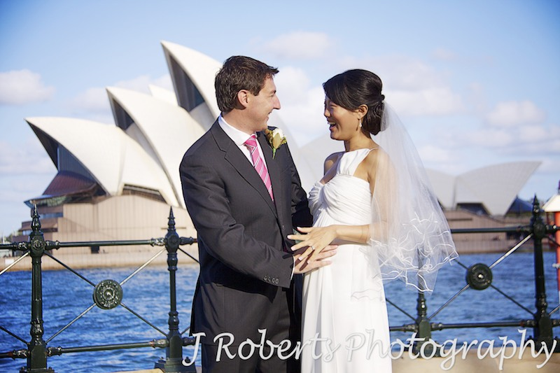Couple laughing with hand on pregnant belly in front of Sydney Opera House - wedding photography sydney
