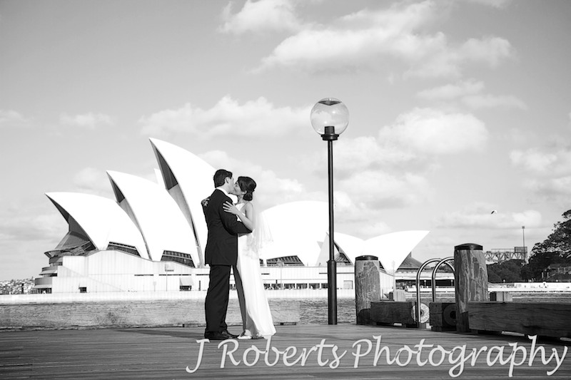 Wedding couple kissing at The Rocks Sydney with Opera House behind - wedding photography sydney