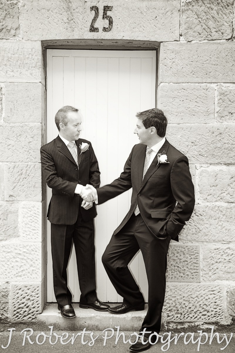 Groom and best man chatting on front of historic doorway the rocks sydney - wedding photography sydney