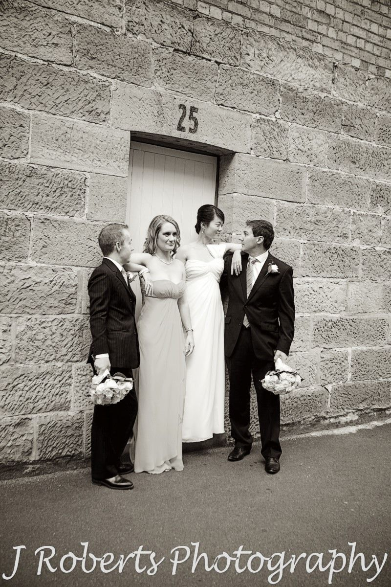 Bridal party being silly in front of doorway the rocks sydney - wedding photography sydney