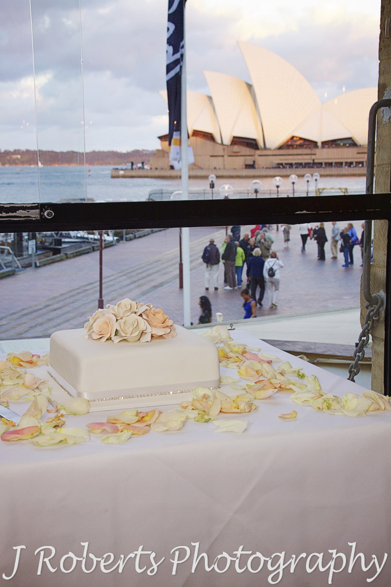 Wedding cake in front of window overlooking the opera house at wolfies grill the rocks - wedding photography sydney