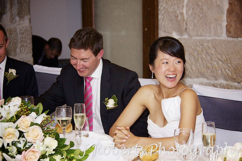 Bride and groom laughing at speeches at the reception - wedding photography sydney