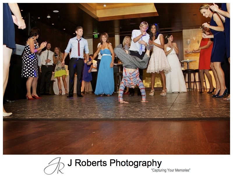 Groovy page boy break dancing at wedding reception - sydney wedding photography
