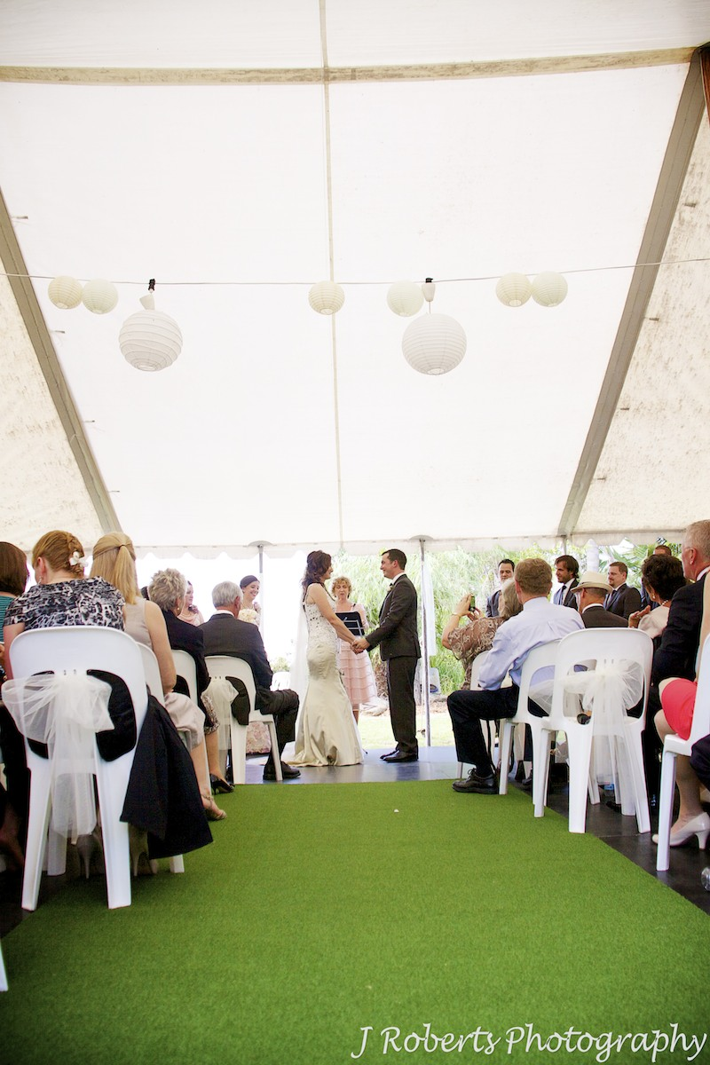 Bride and groom hold hands at head of aisle in outdoor garden wedding - wedding photography sydney