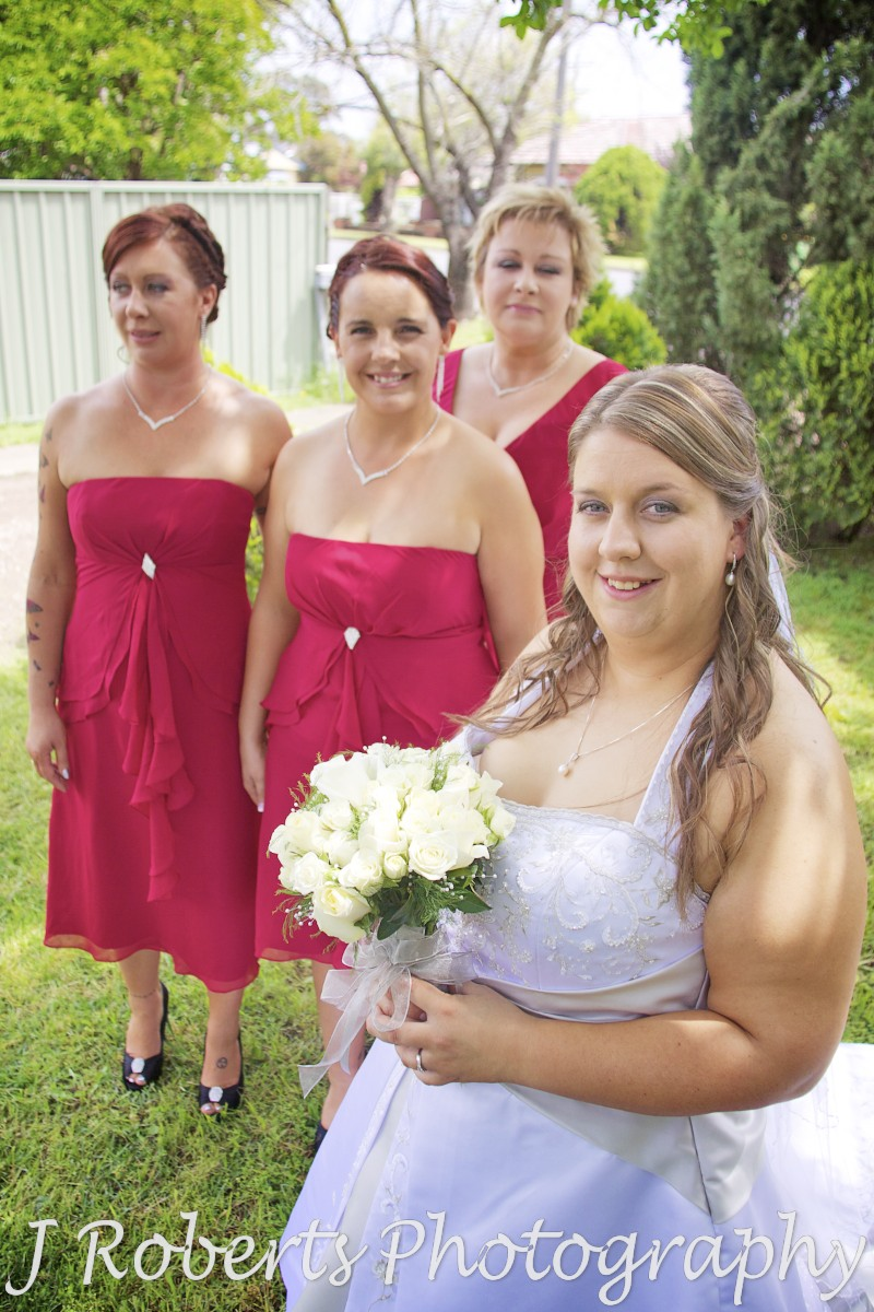 Bride smiling with bridesmaids in red - wedding photography sydney