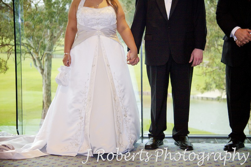 Bride and groom holding hands during ceremony - wedding photography sydney