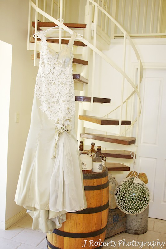 Wedding dress hanging from spiral staircase - wedding photography sydney