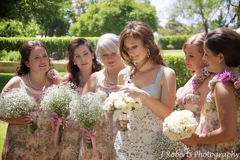 Bride looking at flowers - wedding photography sydney