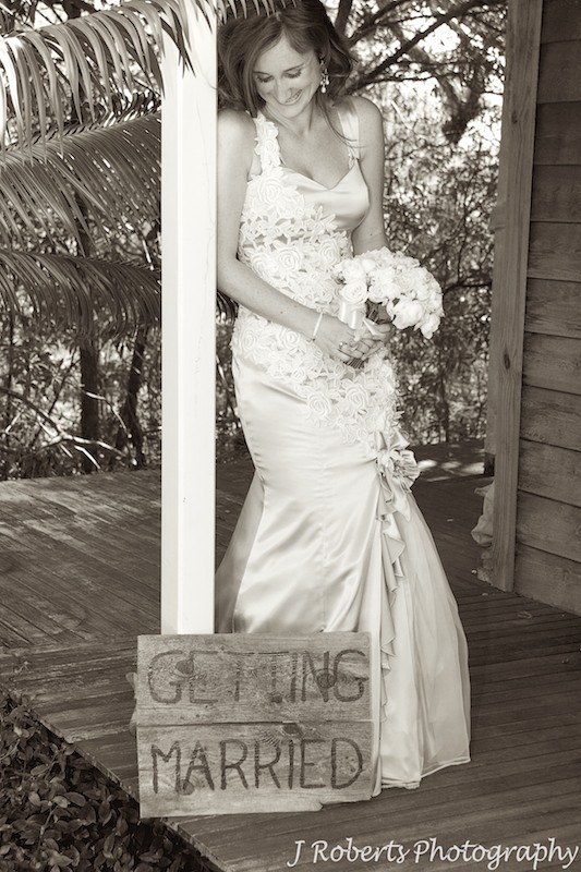 Bride laughing down at getting married sign - wedding photography sydney