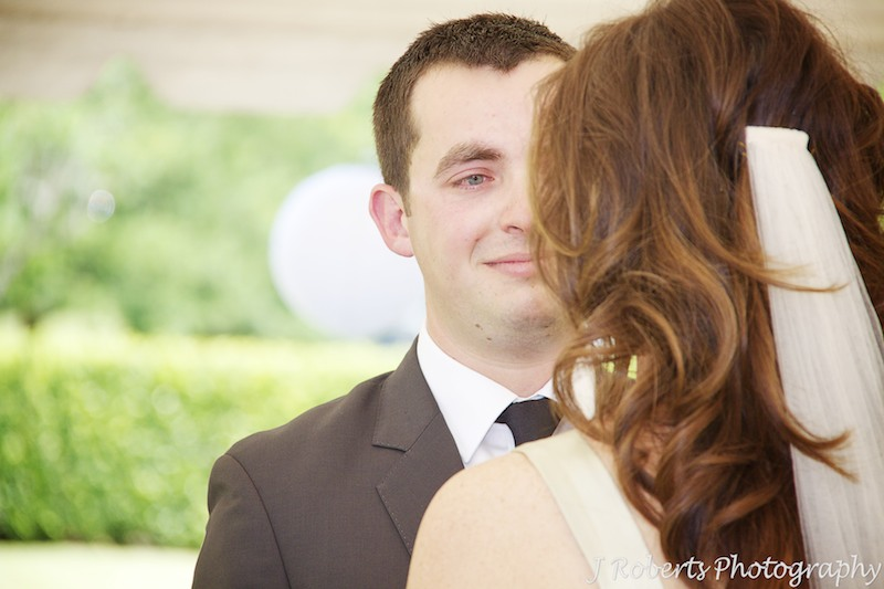 Groom looking into brides eyes during marriage ceremony - wedding photography sydney
