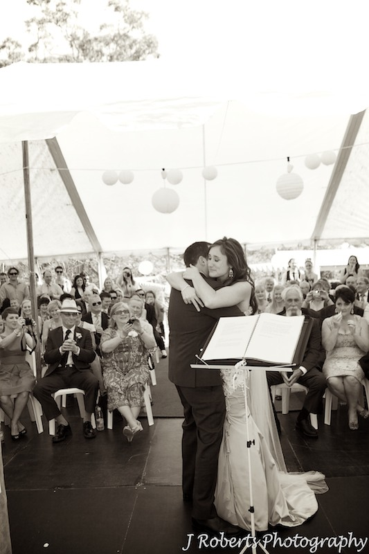 Bride and groom embrace in a garden wedding marquee - wedding photography sydney