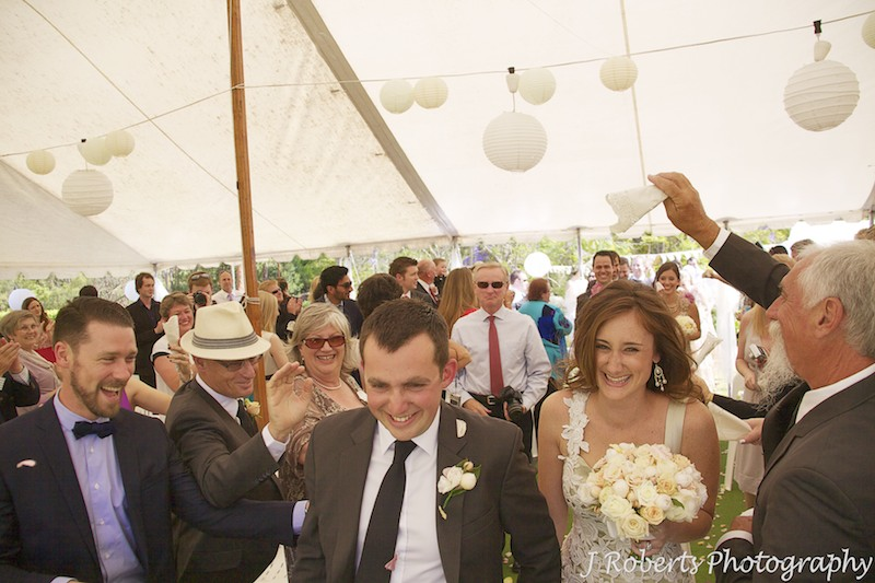 Bride and groom walk down the aisle with pats on their back - wedding photography sydney