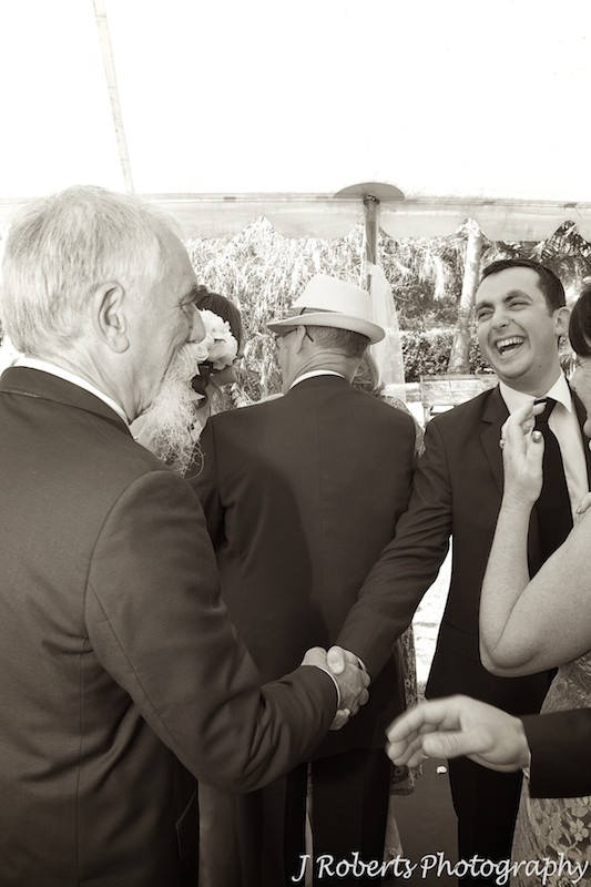 Groom being congratulated by his father in law after marriage ceremony - wedding photography sydney