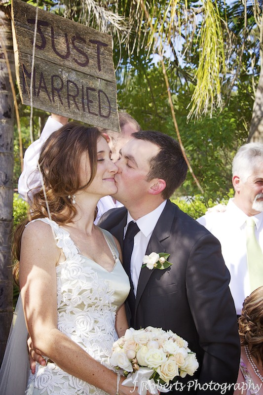 Bride and groom kissing under the